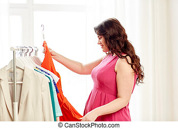 happy plus size woman choosing clothes at wardrobe - ...