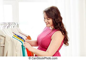 happy plus size woman choosing clothes at wardrobe - ...