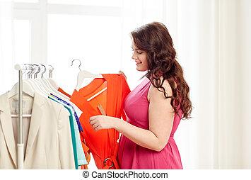 happy plus size woman choosing clothes at wardrobe -...