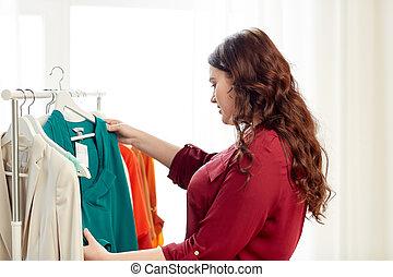 happy plus size woman choosing clothes at wardrobe