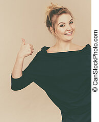 Happy positive blonde woman showing thumb up gesture