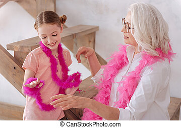 Happy positive girl looking at her feather boa - Like a...