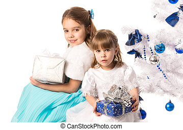 Happy positive girls sisters holding gift boxes