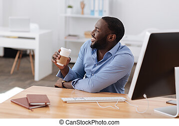 Happy positive man holding a cup of coffee