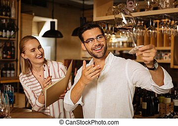 Happy positive man showing a glass of wine