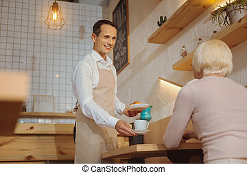 Happy positive waiter looking at his customer
