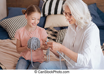 Happy positive woman showing how to knit