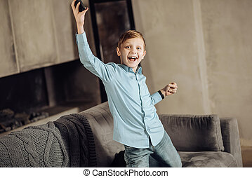 Happy pre-teen boy celebrating victory in game