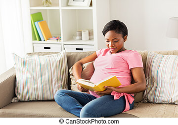 happy pregnant african woman reading book at home