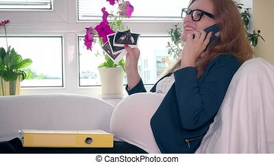 Happy pregnant business woman with ultrasound photo image calling cell phone