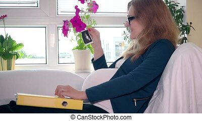 Happy pregnant business woman with ultrasound photo in hand and documents folder