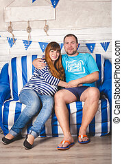 pregnant couple relaxing and hugging on sofa