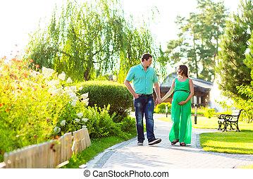 Happy pregnant couple walking at park