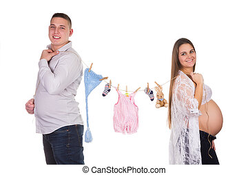 Happy pregnant couple with baby clothes