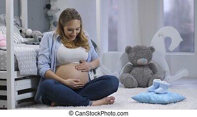 Happy pregnant female feeling baby pushing - Happy amazed...