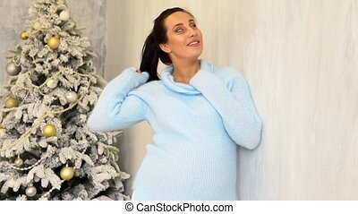 happy pregnant mom by the Christmas tree with Christmas gifts