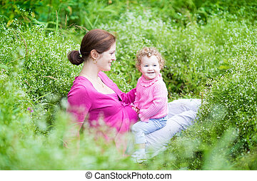 Happy pregnant mother playing with her baby daughter in a beauti