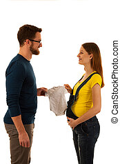Happy pregnant woman and man holding babys dress isolated over white