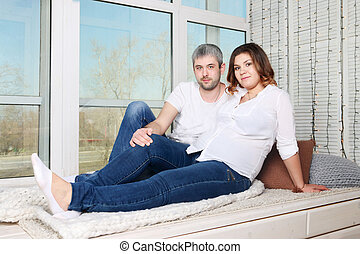 Happy pregnant woman and man in jeans poses in white room with big window