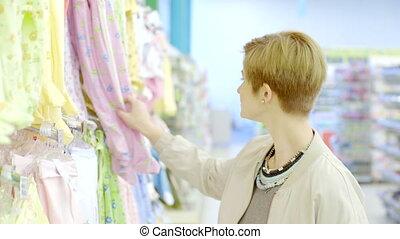 Happy pregnant woman choosing romper suit in supermarket