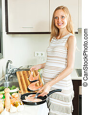 Happy pregnant woman cooking salmon