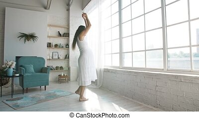 Beautiful pregnant woman in a front of the window