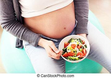 Happy pregnant woman eating salad