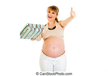 Happy pregnant woman holding gift for her baby and showing thumbs up gesture isolated on white
