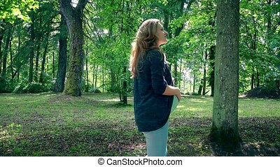 Happy pregnant woman in ninth month pregnancy walk in park...