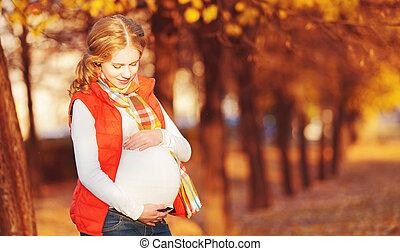 Happy pregnant woman on autumn walk