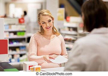 happy pregnant woman prescription at pharmacy
