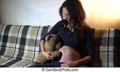 Happy pregnant woman resting on a sofa and stroking her tummy.