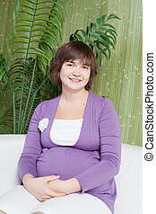 happy pregnant woman sits on a sofa