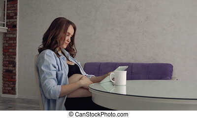 Happy pregnant woman sitting at a glass kitchen table drinking coffee and using a tablet computer. Watch online lecture from the doctor