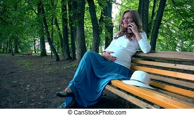 Happy pregnant woman sitting on bench and talking phone. Female stroke belly