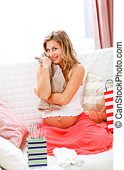 Happy pregnant woman sitting on sofa with shopping bags and hugging baby clothes