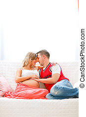 Happy pregnant woman sitting with husband on couch and hugging