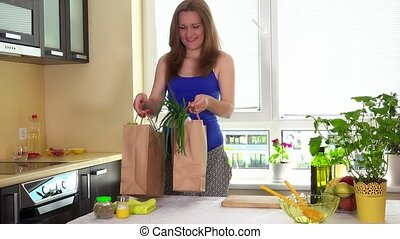Happy pregnant woman unload paper bags with organic healthy vegetables
