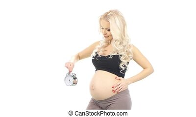 Happy pregnant woman with alarm clock expecting baby, white