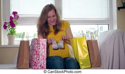 Happy pregnant woman with colorful bags sit on sofa back...