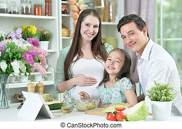 Happy pregnant woman with husband and daughter preparing salad together at kitchen