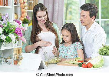 happy pregnant woman with husband and daughter preparing salad