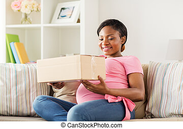 happy pregnant woman with parcel box at home