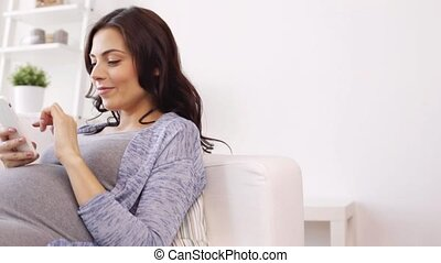happy pregnant woman with smartphone at home