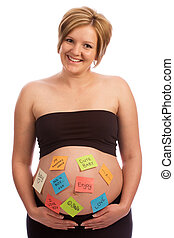 Happy pregnant woman with sticky notes on belly