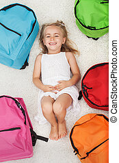 Happy preschool girl lying among colorful school bags