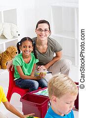happy preschool teacher and student