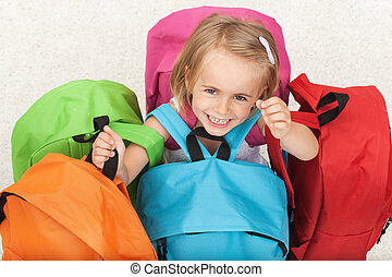 Happy preschooler girl choosing her school bag from a colorful set