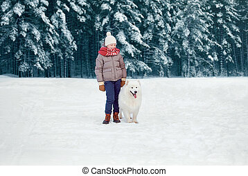 Happy preteen boy walking with his white Samoyed dog in winter snowy day over trees forest background