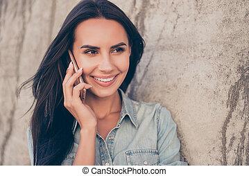 Happy pretty brunette girl talking on mobile phone
